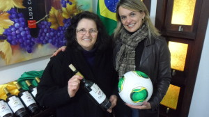 Dona Isabel Carraro, matriarca da família que administra a Lídia Carraro, (à esq.) com o vinho oficial da Copa do Mundo 2014 - Faces e eu (à dir.) com a bola oficial da Copa do Mundo 2014.