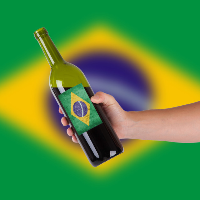 Hand holding a bottle of red wine, label of Brazil, isolated on white,