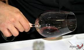 examinando o brilho e a transparência do vinho, primeiro olhando de cima da taça, através da luz ou contra um fundo branco, com a taça ligeiramente inclinada