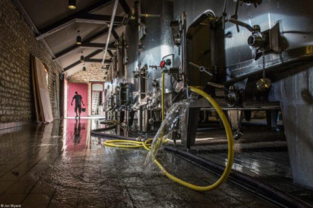 Cleaning the Cuvery, no Domaine Faiveley, do fotógrafo britânico John Wyand   Os tanques de madeira e aço inoxidável usados para fermentar o vinho tinto são esvaziados e o restante do material da uva é pressionado