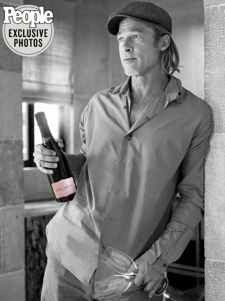 Brad Pitt segurando a garrafa de Fleur de Minalva